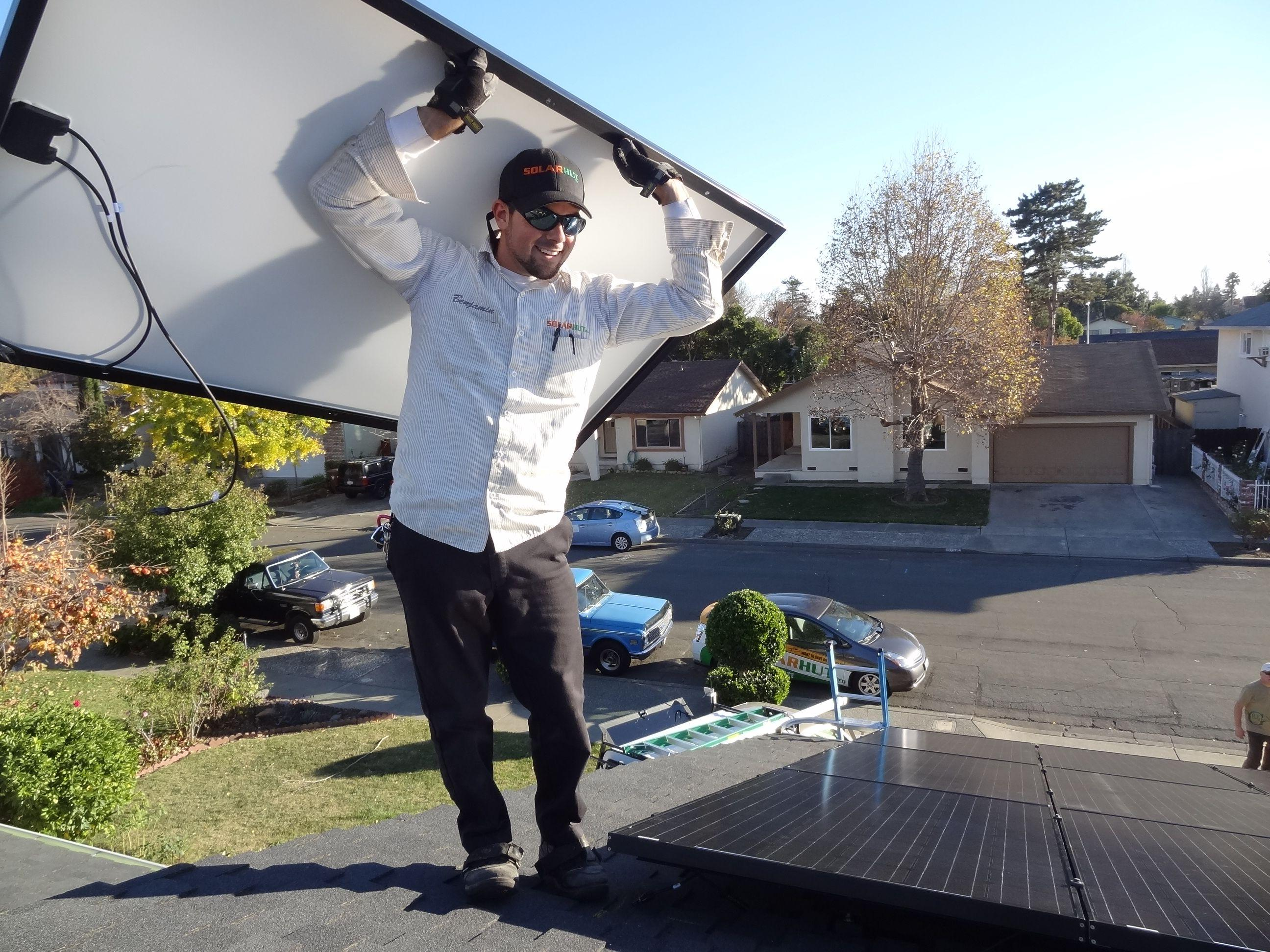 Technician carrying solar panel up on a roof