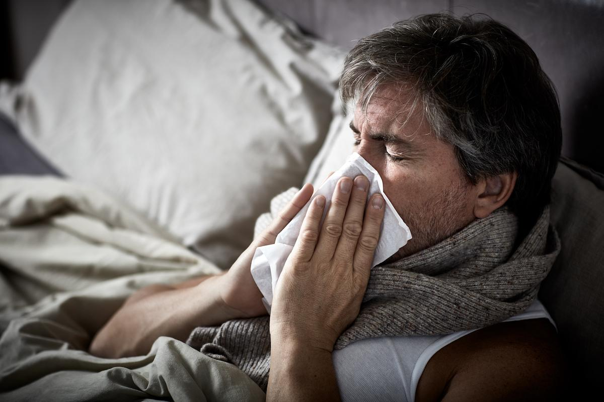 Man with cold blowing nose into a tissue